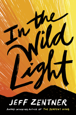 Book cover: In the Wild Light. The Text is scrawled in a black handwritten font, across streaks of orange and yellow.
